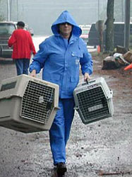 Person in rain gear carrying two pet carriers.