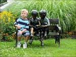 A little boy sits with a statue of a little boy and little girl reading - photograph