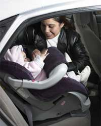 woman putting a child into a safety seat - photograph
