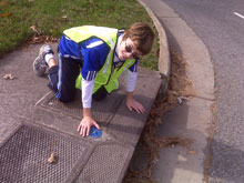 Russell Martin placing a medallion on a storm drain in his neighborhood. - photo