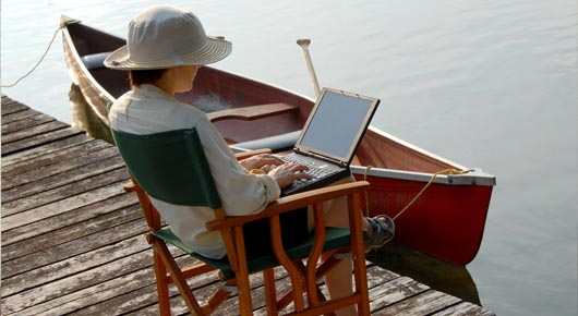 Sitting on a dock using a laptop with canoe in water