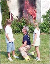 A firefighter talks to a boy and a girl about fire safety - photograph