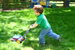 Boy playing with toy lawnmower - photograph